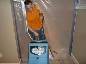 Water Damage Restoration Technician Using Air Mover Near Vapor Barrier
