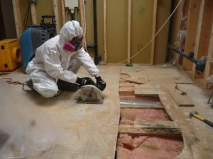 water damage restoration expert fixing floorboards