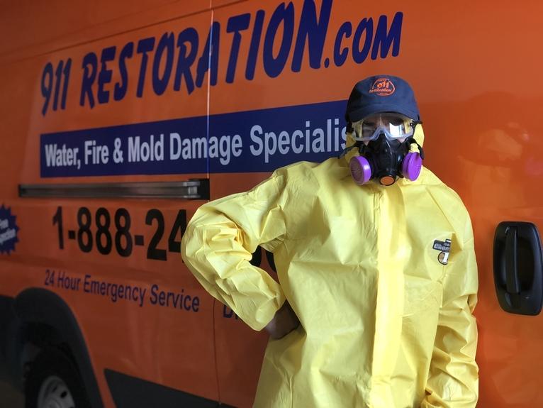 water damage restoration technician in front of 911 Restoration van