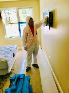fire damage restoration technician in hazmat suit