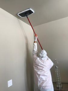 a fire damage restoration technician cleans a ceiling