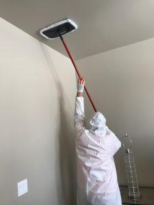 a fire damage restoration technician cleans a ceiling